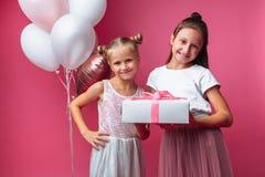 Het portret van een tiener op een roze achtergrond, met giften, verjaardagsconcept, één geeft een ander meisje een gift stock fotografie