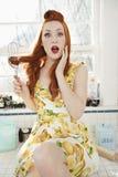Het portret van een verraste jonge vrouw met binnen verward haar zwaait zitting op keukenteller Royalty-vrije Stock Afbeeldingen