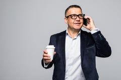 Het portret van een vrolijke rijpe mens kleedde zich in overhemd houdend meeneemkoffiekop terwijl het gebruiken van mobiele die t royalty-vrije stock fotografie