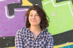 Het portret van een vrouw die in die de haar medio jaren '30 met groene ogen ontspande tegen een muur glimlachen met graffiti wor Royalty-vrije Stock Foto