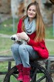 Het portret van een vrouw kleedde zich in rood met een kat in haar wapens royalty-vrije stock fotografie
