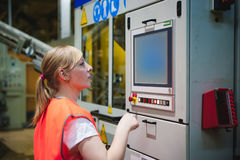 Het portret van een vrouwelijke werknemer in een oranje robevest in de het werk ruimte van een productiefaciliteit, controleert e Stock Foto