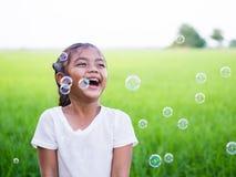 Het portret van een weinig Aziatisch meisje lacht en geniet van met bubbl Stock Afbeeldingen