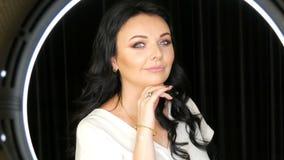 Het portret van een zeer Mooi blauw-eyed vrouwenmodel met lang zwart haar en de mooie avond maken het stellen voor op stock videobeelden