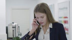Het portret van een zekere glimlachende mooie bedrijfsvrouw of de secretaresse in een bedrijfs strikt kostuum die op een cel spre stock video