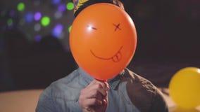 Het portret van een zekere jonge mens die in verjaardagshoed een ballon verwijderen schilderde met grappig gezicht kijkend in de  stock video