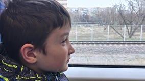 Het portret van eenzame droevig, gedeprimeerd en apathisch preteen jongen die op een trein berijden, hij die van huis ontsnappen stock footage