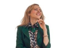 Het portret van elegante jonge blonden in een groen jasje dat uw hand dichtbij de Kin houdt ziet weg eruit en glimlachend Stock Foto
