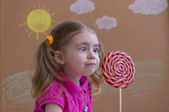 Het portret van emotioneel meisje met grote suikerlolly, jong geitje eet snoepjes achtergrond van geschilderde zon en witte wolke Royalty-vrije Stock Foto