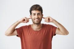 Het portret van geërgerde jonge mannelijke Kaukasisch met gesloten ogen het stoppen van zijn oren met vingers kan de tribune hevi royalty-vrije stock foto's