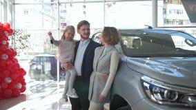 Het portret van gelukkig familiepaar van de consument die met jong geitjemeisje op handen toont sleutels aan auto bij autotoonzaa stock videobeelden