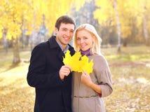 Het portret van gelukkig jong glimlachend paar met gele esdoorn doorbladert de herfst stock foto's