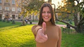 Het portret van gelukkig Kaukasisch donkerbruin meisje maakt de vinger tot show zoals en eerbied op groene parkachtergrond stock videobeelden