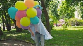 Het portret van gelukkig meisje stelt en draait zich bij camera met ballons in park om stock videobeelden