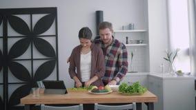 Het portret van gelukkige echtgenoot en vrouw in keuken, jonge familie bereidt gezonde maaltijd voor brunch met groenten op keuke stock videobeelden