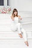 Het portret van gelukkige glimlachende jonge mooie vrouw in witte toevallige kleding, het tonen beduimelt omhoog gebaar, Royalty-vrije Stock Foto