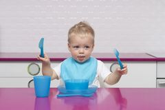 Het portret van Gelukkige Jonge Babyjongen in een blauwe slab met vork en mes in van hem dient Hoge Stoel in de moderne keuken in stock foto