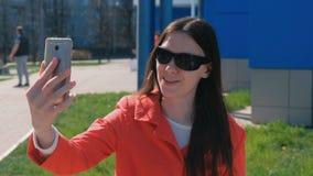 Het portret van gelukkige jonge donkerbruine vrouw in zonnebril maakt selfie op de telefoon naast de blauwe bouw op de straat stock video