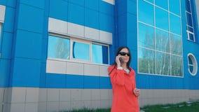 Het portret van gelukkige jonge donkerbruine vrouw in zonnebril spreekt op de telefoon naast de blauwe bouw stock videobeelden
