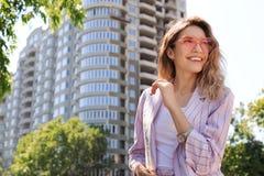 Het portret van gelukkige jonge vrouw met hart vormde glazen in stad op zonnige dag stock fotografie