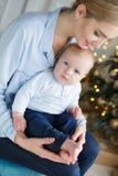 Het portret van gelukkige moeder en de aanbiddelijke baby vieren Kerstmis Stock Fotografie
