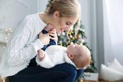 Het portret van gelukkige moeder en de aanbiddelijke baby vieren Kerstmis Stock Afbeeldingen