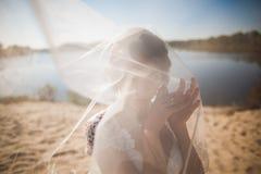 Het portret van gelukkige mooie bruid met hoofd behandelde bridalveil, zich bevindt op strand in huwelijksdag Stock Afbeelding