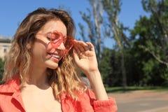 Het portret van gelukkige vrouw met hart vormde glazen in stad op zonnige dag stock foto's