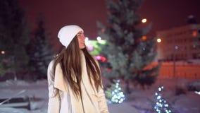 Het portret van gelukkige vrouw na het winkelen in de stad in Kerstmis verfraaide straten, langzame motie De mooie vrouw koopt stock videobeelden