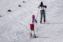 Het portret van gemiddelde lengte van een gelukkige skiër die zich met skis op de helling bevinden die bij de camera in een blauw Royalty-vrije Stock Fotografie
