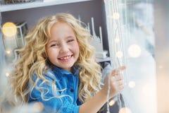 Het portret van glimlachend mooi meisje zit op de vensterbank royalty-vrije stock afbeeldingen