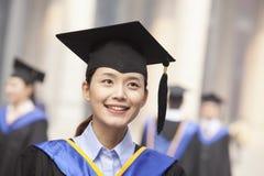 Het portret van glimlachende jonge vrouwelijke gediplomeerde in graduatietoga en baret met kameraad behaalt op achtergrond een dip Royalty-vrije Stock Fotografie