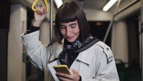 Het portret van glimlachende mooie jonge vrouw in openbaar vervoer houdt de leuning en het doorbladeren op gele smartphone Stad stock videobeelden