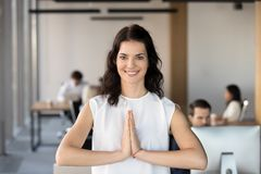 Het portret van glimlachende vrouwelijke werknemer mediteert in gebed stelt stock fotografie