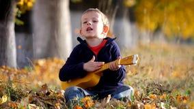 Het portret van grappig kind zingt bij gitaar, dient het gelukkige jonge geitje die van hem slaan park in stock videobeelden