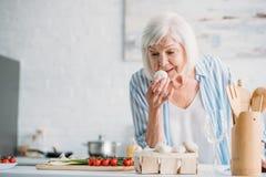 het portret van het grijze haardame controleren schiet terwijl het koken van diner bij teller als paddestoelen uit de grond royalty-vrije stock afbeelding