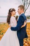 Het portret van het gelukkige jonge onlangs weg echtpaar stellen op de herfst lakeshore volledige sinaasappel gaat royalty-vrije stock fotografie