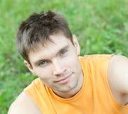 Het portret van het gezicht van mensenzitting op een gras Royalty-vrije Stock Foto's