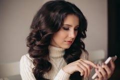 Het portret van het jonge mooie donkerbruine vrouw spreken op de telefoon, schrijft SMS Droevige student met de in hand telefoon Royalty-vrije Stock Fotografie