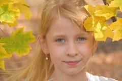 Het portret van het kind in de herfstbladeren Stock Afbeelding