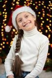 Het portret van het kindmeisje in Kerstmisdecoratie, gekleed in Kerstmanhoed, boke lichten op donkere achtergrond, het concept va Royalty-vrije Stock Foto
