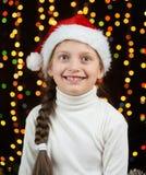 Het portret van het kindmeisje in Kerstmisdecoratie, gekleed in Kerstmanhoed, boke lichten op donkere achtergrond, het concept va Royalty-vrije Stock Foto's