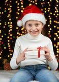 Het portret van het kindmeisje in Kerstmisdecoratie, gekleed in Kerstmanhoed, boke lichten op donkere achtergrond, het concept va Royalty-vrije Stock Afbeelding