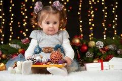 Het portret van het kindmeisje in Kerstmisdecoratie, gelukkige emoties, het concept van de de wintervakantie, donkere achtergrond Stock Afbeeldingen