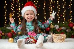 Het portret van het kindmeisje in Kerstmisdecoratie, gelukkige emoties, het concept van de de wintervakantie, donkere achtergrond Stock Foto's