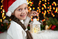Het portret van het kindmeisje met Kerstmisdecoratie, de donkere achtergrond met lichten, de gezichtsuitdrukking en de gelukkige  Royalty-vrije Stock Afbeelding