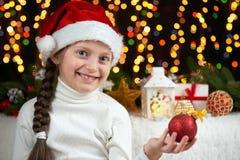 Het portret van het kindmeisje met Kerstmisdecoratie, de donkere achtergrond met lichten, de gezichtsuitdrukking en de gelukkige  Royalty-vrije Stock Foto
