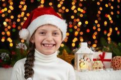 Het portret van het kindmeisje in santahoed met Kerstmisdecoratie, donkere achtergrond met lichten, gezichtsuitdrukking en gelukk Stock Foto