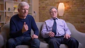 Het portret van hogere mannelijke vrienden die op voetbal samen op TV letten en wordt teleurgesteld na het verlies stock footage