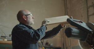 Het portret van hogere timmerman controleert de kwaliteit schurend houten raad in vervaardiging stock video